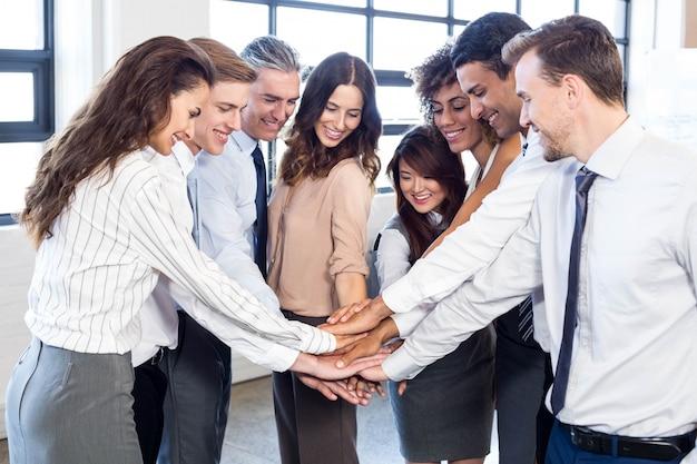 Gens d'affaires empiler des mains et souriant au bureau