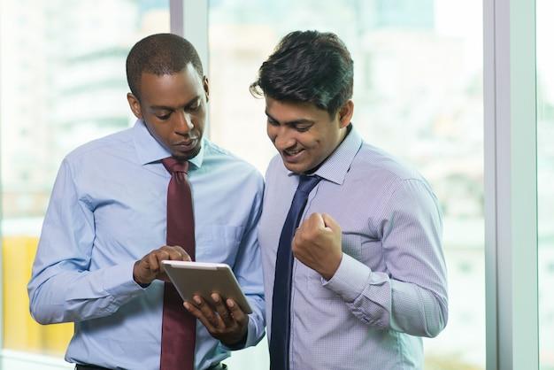 Des gens d'affaires enthousiastes en train de lire de bonnes nouvelles sur des tablettes