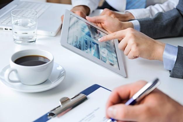 Gens d'affaires faisant un rapport à l'aide d'une tablette, café dans une tasse