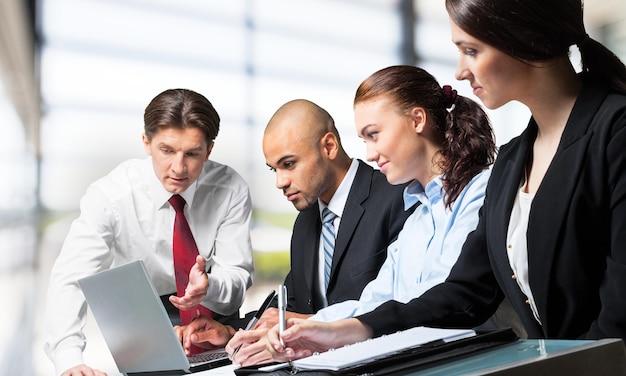 Gens d'affaires faisant un rapport à table avec des graphiques isolés sur blanc