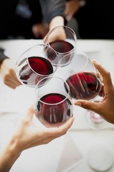 Gens d'affaires grillant du vin rouge au bureau