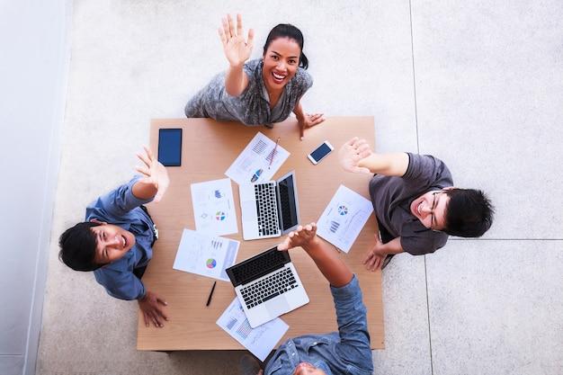 Gens d'affaires heureux célèbrent au-dessus de la table en réunion au bureau mobile