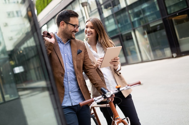 Gens d'affaires heureux discutant et souriant tout en marchant ensemble en plein air