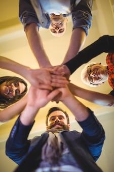Gens d'affaires heureux empiler les mains dans le bureau créatif