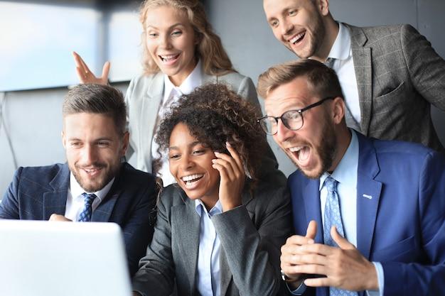 Les gens d'affaires heureux rient près d'un ordinateur portable au bureau. les collègues de l'équipe qui réussissent plaisantent et s'amusent ensemble au travail.
