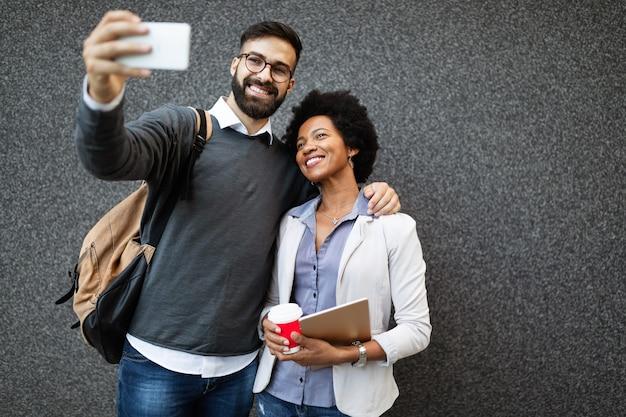 Gens d'affaires heureux utilisant des gadgets d'appareils technologiques près du mur d'un bâtiment moderne