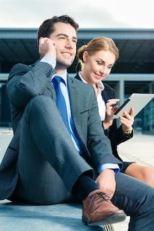 Gens d'affaires ou homme d'affaires et femme d'affaires travaillant en plein air, à l'aide d'un ordinateur portable ou d'une tablette et d'un téléphone portable