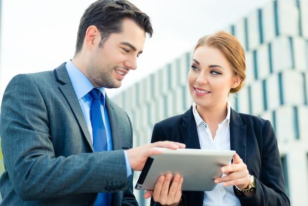Gens d'affaires ou homme d'affaires et femme d'affaires travaillant en plein air, à l'aide d'un ordinateur portable ou d'une tablette