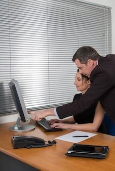 Gens d'affaires, homme et femme, réunion et utilisation d'un ordinateur