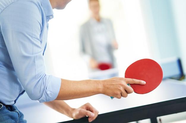 Gens d'affaires jouant au tennis de table dans un espace de bureau partagé