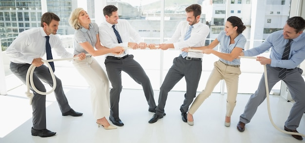 Gens d'affaires jouant du tir à la corde au bureau