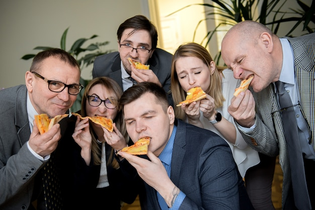 Gens d'affaires, manger de la pizza au bureau