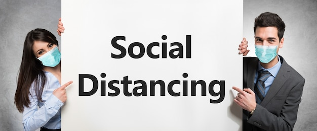 Gens d'affaires masqués tenant un tableau blanc avec le texte distance sociale