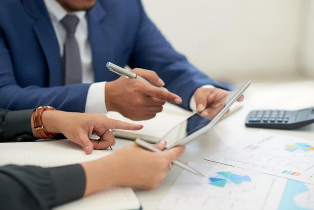 Gens d'affaires méconnaissables assis à la réunion avec des graphiques, regardant et pointant sur une tablette