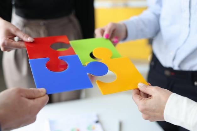 Gens d'affaires mettant ensemble puzzle coloré gros plan
