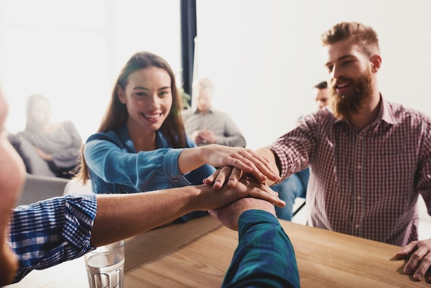 Les gens d'affaires mettent leurs mains ensemble au bureau. concept de travail d'équipe et de partenariat