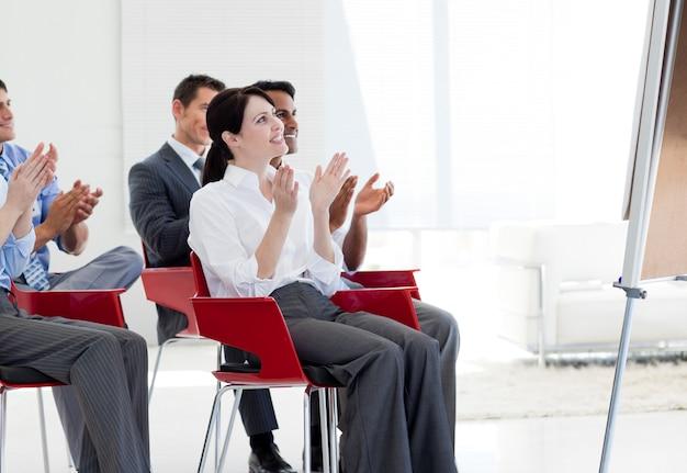 Les gens d'affaires multiethniques applaudissent à la fin d'une conférence
