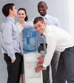 Gens d'affaires multiethniques confiants interagissant à un watercooler