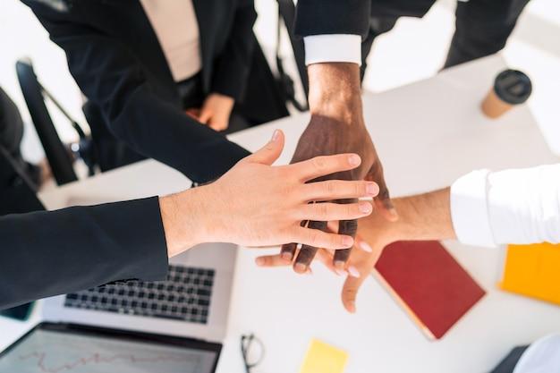 Gens d'affaires multiraciaux jalonnant la main ensemble