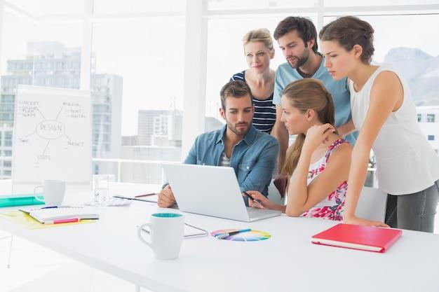 Gens d'affaires occasionnels utilisant un ordinateur portable ensemble