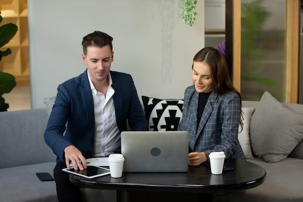 Gens d'affaires parlant au bureau à l'aide d'une tablette numérique et d'un ordinateur