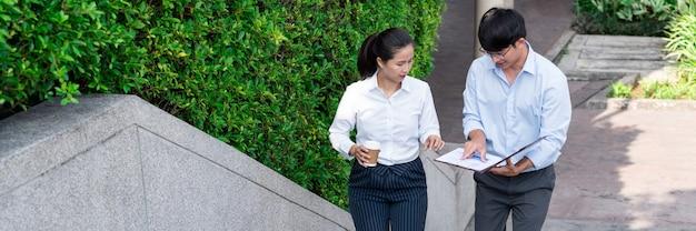 Des gens d'affaires parlent pendant la pause pour discuter d'un nouveau projet à l'extérieur du bureau de la ville.