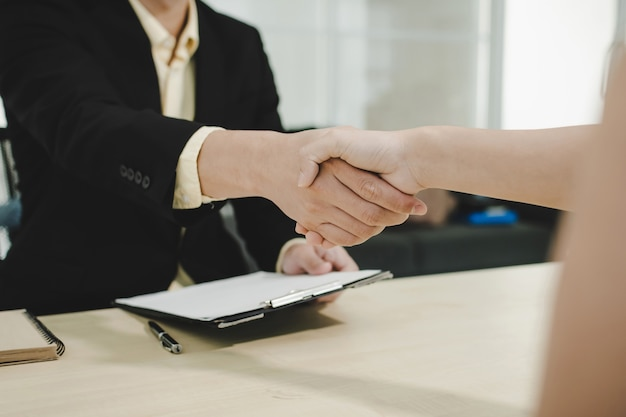 Les gens d'affaires partenaire se serrant la main après la signature d'un contrat de bureau dans la salle de réunion