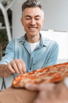 Les gens d'affaires sur la pause déjeuner, manger de la pizza