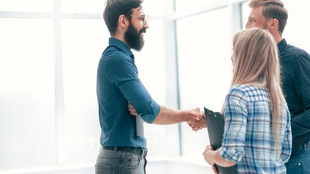 Gens d'affaires de poignée de main dans le hall de bureau. notion de coopération