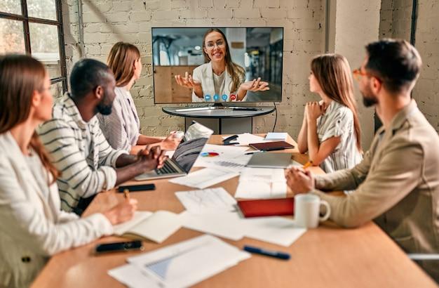 Les gens d'affaires portant un masque facial, se réunissent, discutent, réfléchissent à des idées d'investissement dans le bureau pendant le coronavirus