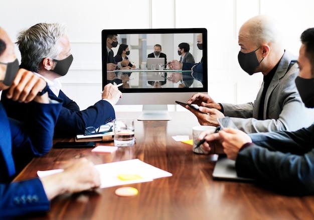 Gens d'affaires portant des masques lors d'une réunion sur le coronavirus
