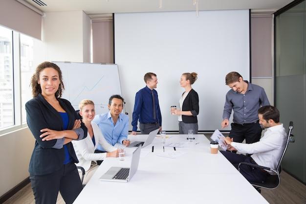 Les gens d'affaires posant sourire dans une salle de réunion