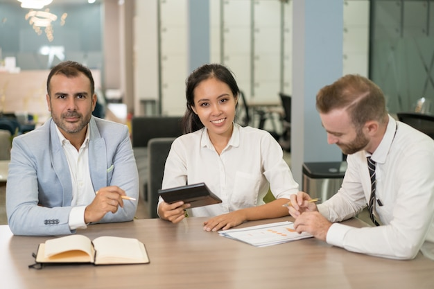 Gens d'affaires positifs travaillant avec un diagramme au bureau