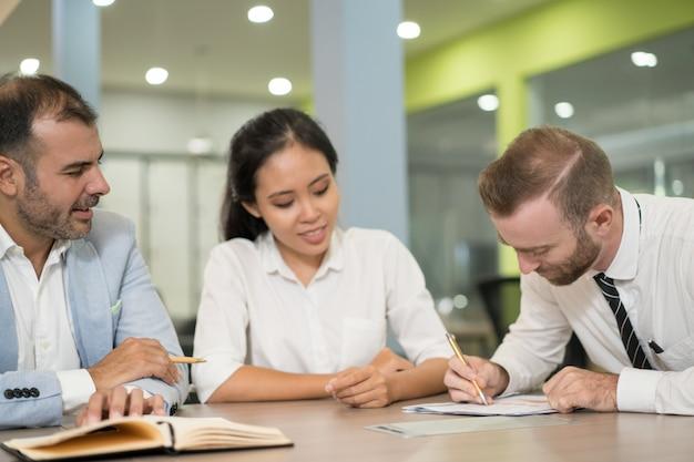 Les gens d'affaires positifs travaillent ensemble dans le bureau