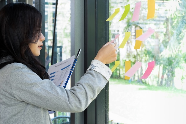 Les gens d'affaires le poster note l'idée de discuter et de planification dans le mur de verre à la salle de réunion