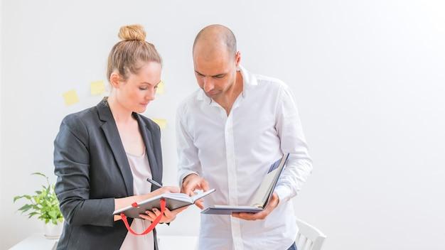 Les gens d'affaires professionnels examinent les horaires dans un journal au lieu de travail
