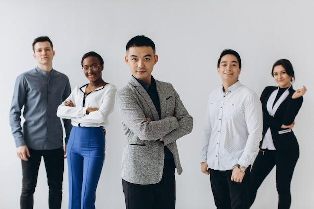 Gens d'affaires professionnels multiraciaux gais rire ensemble debout en ligne près du mur, groupe d'étudiants de divers employés heureux divers, équipe de personnel d'entreprise s'amusant, concept de ressources humaines