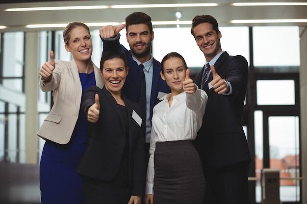 Gens d'affaires prospères montrant le signe du pouce vers le haut