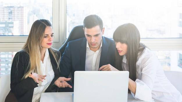 Gens d'affaires à la recherche à un ordinateur portable ayant une discussion lors de la réunion