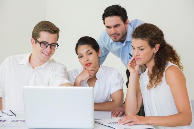 Gens d'affaires à la recherche d'un ordinateur portable