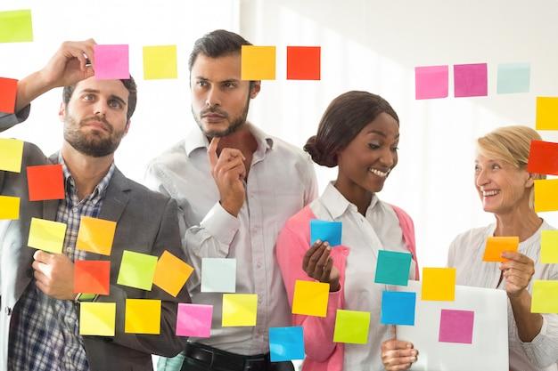 Gens d'affaires regardant des notes adhésives