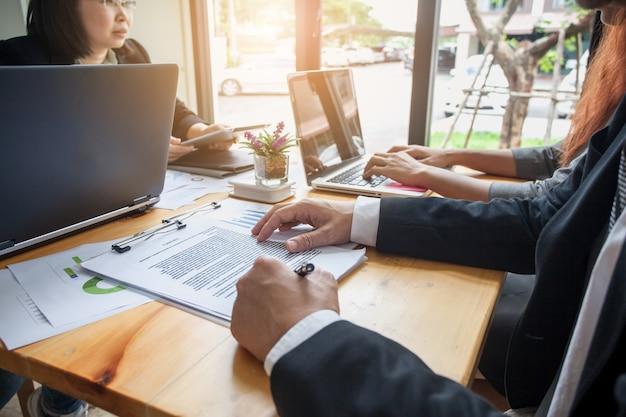 Les gens d'affaires réunis à travailler avec des rapports financiers. signature d'un contrat d'entreprise.