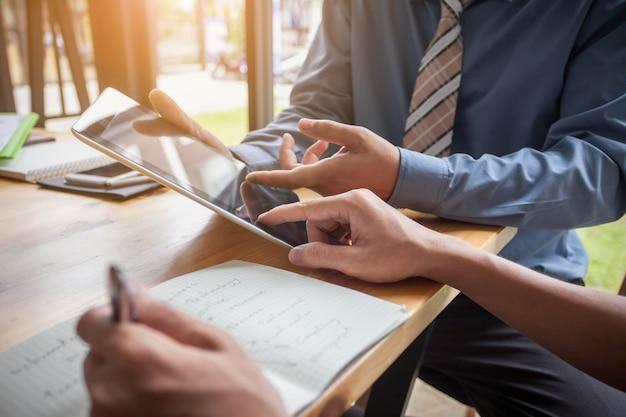Les gens d'affaires réunis à travailler avec des rapports financiers et une tablette.