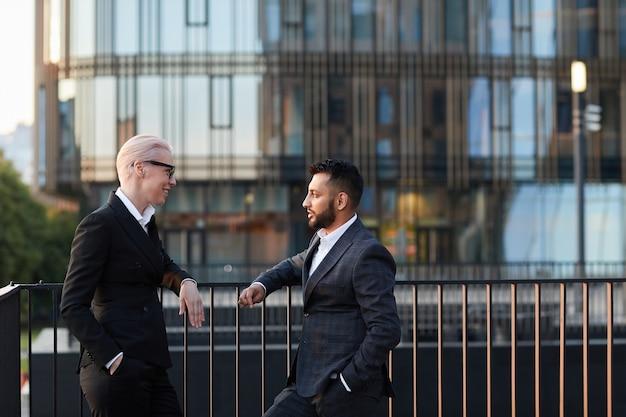 Les gens d'affaires se parlent debout sur un balcon contre les bâtiments modernes