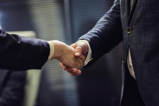 Les gens d'affaires se serrant la main après avoir terminé une réunion comme accord