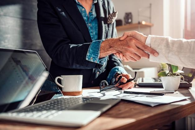 Gens d'affaires se serrant la main après une réunion réussie