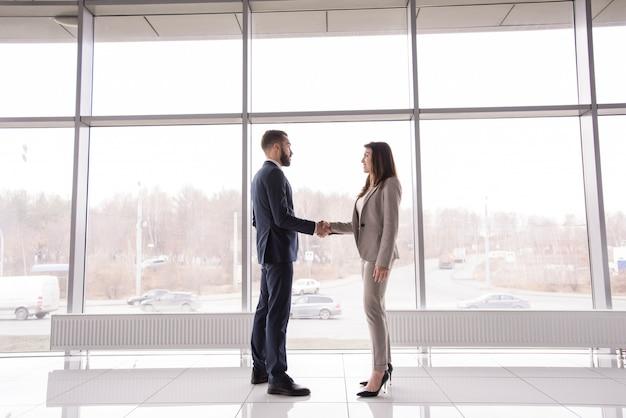 Gens d'affaires se serrant la main contre la fenêtre
