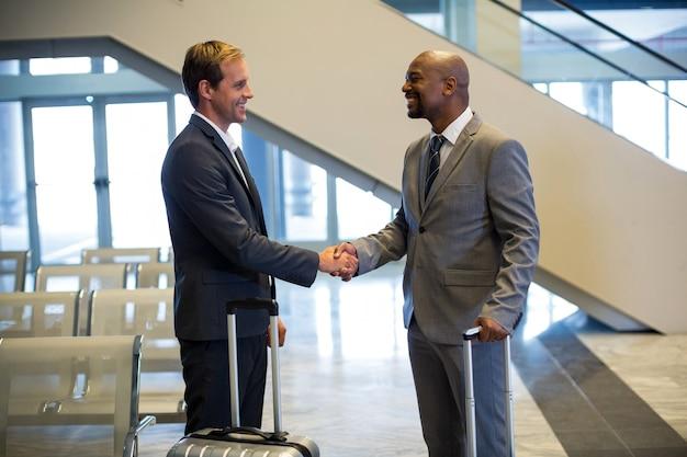 Gens d'affaires se serrant la main dans la zone d'attente