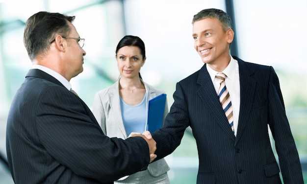 Les gens d'affaires se serrant la main lors d'une réunion sur fond