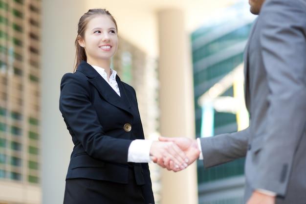 Les gens d'affaires se serrant la main en plein air